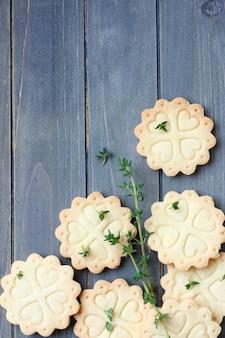 Galletas de torta dulce libres hechas en casa del gluten con las ramas del tomillo en viejo fondo de madera
