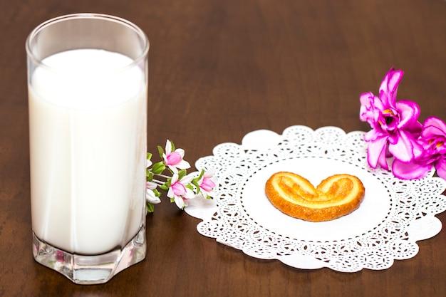 Galletas y un vaso de leche: desayuno saludable. mesa de madera. de cerca.