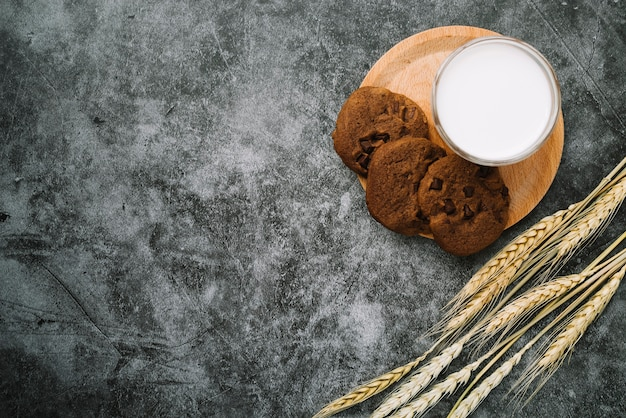 Galletas y vaso de leche con espigas de trigo sobre fondo de hormigón teñido