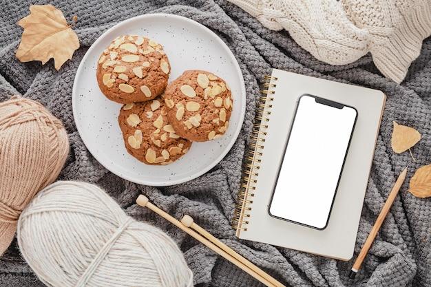 Galletas de vista superior, hilo y agenda en manta con teléfono en blanco