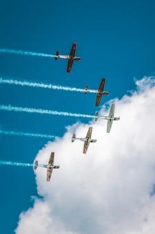 Gama de aviones preparando un espectáculo aéreo bajo el impresionante cielo nublado
