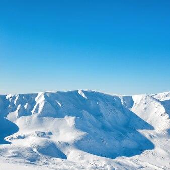 Gama de picos de las montañas de invierno blanco con nieve