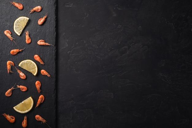 Gambas crudas frescas o camarones rojos hervidos con las especias y el limón en piedra de la pizarra en fondo de piedra oscuro. mariscos, vista desde arriba, plano, copia espacio.