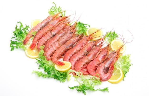 Gambas frescas crudas con ensalada y rodajas de limón sobre fondo blanco.