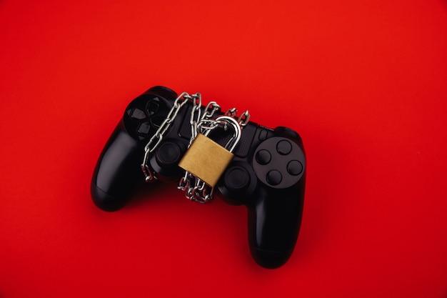Gamepad con cadena y candado sobre fondo rojo.