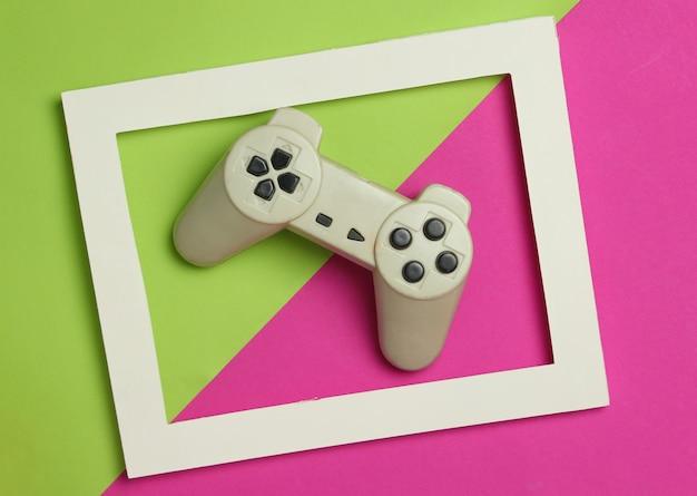 Gamepad en un marco blanco sobre un fondo coloreado. vista superior, minimalismo.