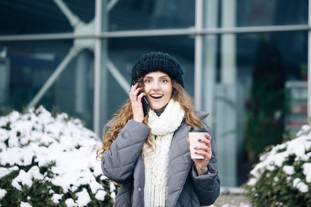 Ganador de mujer emocionada gritando sí regocijándose éxito en el teléfono móvil.