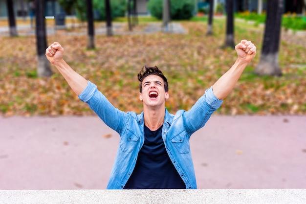 Ganador de todos los días. hombre joven emocionado que mantiene los brazos levantados y que expresa positividad mientras que se sienta al aire libre