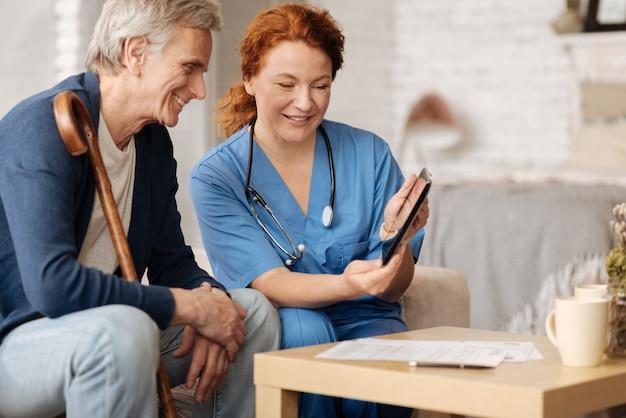 Ganancia de salud. señora inteligente calificada que emplea su tableta para mostrar algunos datos sobre la salud del hombre y explicar las tendencias positivas