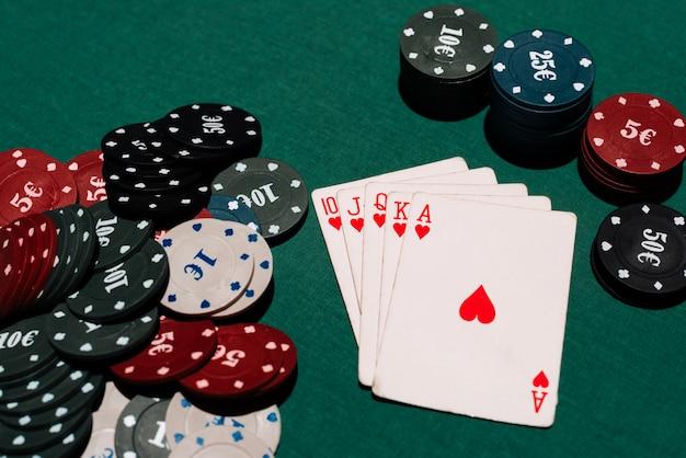 Ganar un juego de póker en el casino. escalera real y un banco de fichas en el fondo de la mesa verde