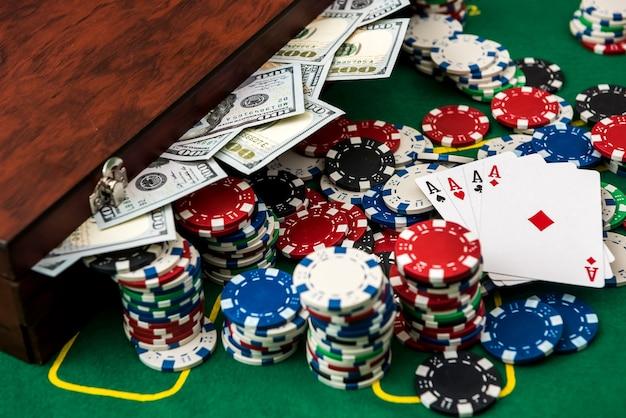 Ganas en un casino. una maleta llena de dinero con fichas y cartas en la mesa de póquer