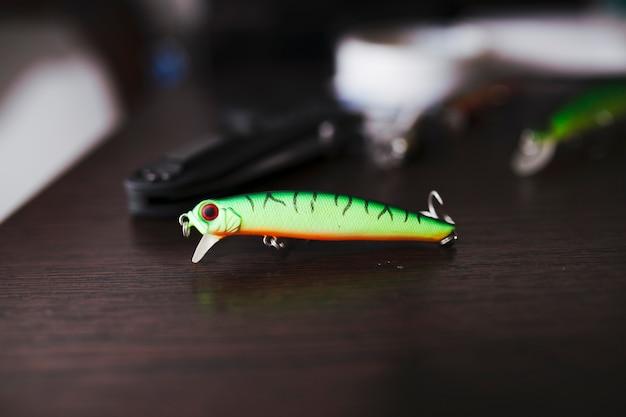 Gancho de pesca de color verde en el escritorio de madera