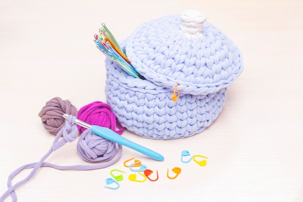 Ganchos en una canasta tejida de hilo. al lado hay bolas de hilo sobre la mesa. hobby y concepto de tejer.