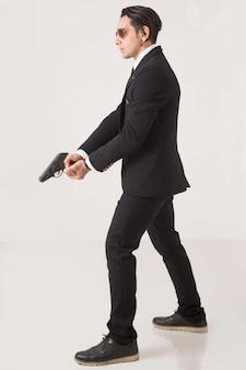 Un gángster en business suite actuando con un arma sobre fondo blanco.