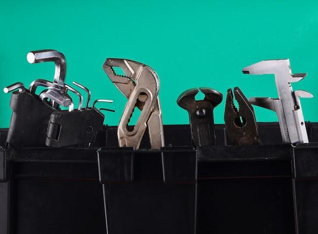 Garaje caja de herramientas de plástico con herramientas de trabajo aisladas en azul. pinzas, llave inglesa, llave hexagonal