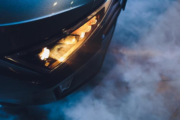 En el garaje del salón del automóvil, centre los faros del automóvil muy cerca, encendiéndose y apagándose verificando las dimensiones de la luz delantera