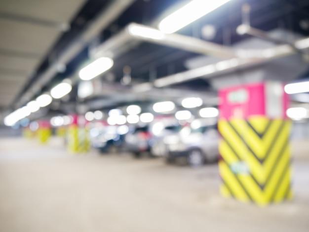 Garaje subterráneo con coches, interior industrial. luz de neón en edificio industrial brillante.