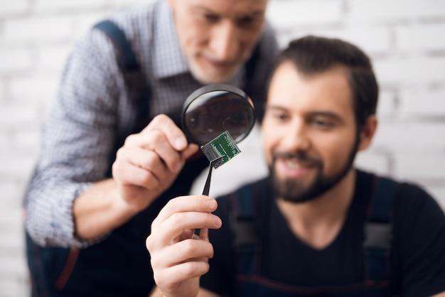 Garantía de reparación de microchip examining con lupa.