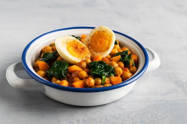 El garbanzo y la espinaca españoles guisan con los huevos en fondo gris claro. cocina española.