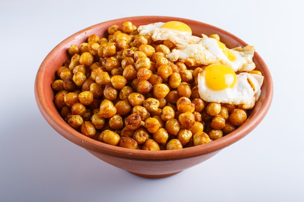 Garbanzos fritos con huevos de codorniz y especias en un plato de arcilla aislado sobre fondo blanco.