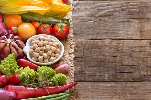 Garbanzos orgánicos secos en un recipiente con verduras crudas en una mesa de madera de cerca con espacio de copia