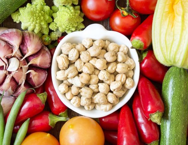 Garbanzos orgánicos secos en un tazón entre las verduras crudas vista superior