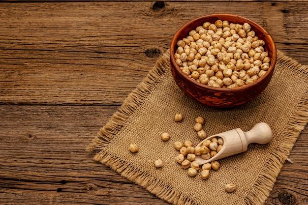 Garbanzos secos en un tazón de cerámica en la mesa de madera vieja. ingrediente tradicional para cocinar hummus