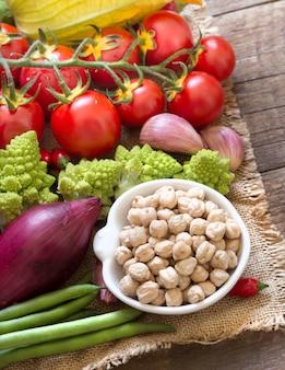 Garbanzos en un tazón con verduras crudas de cerca en una mesa de madera