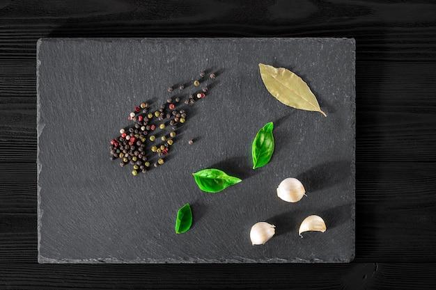 Garlick hinojo pimienta de basílica sobre una piedra negra