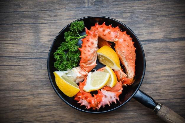 Garras de cangrejo cocidas en una sartén con alaska king crab seafood en mesa de comedor
