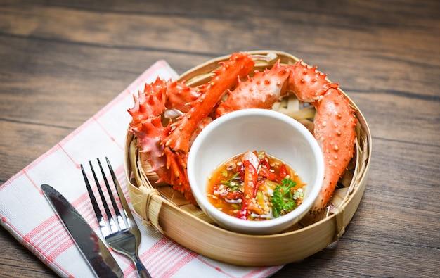 Garras de cangrejo cocidas en vapor de bambú con salsa de cangrejo de alaska y mariscos en la mesa de comedor