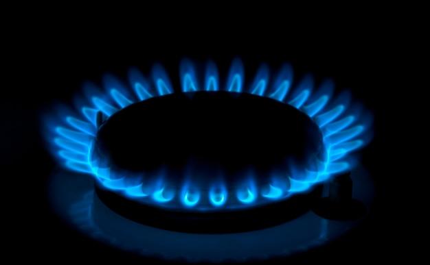 Gas natural quemando llamas azules sobre fondo negro