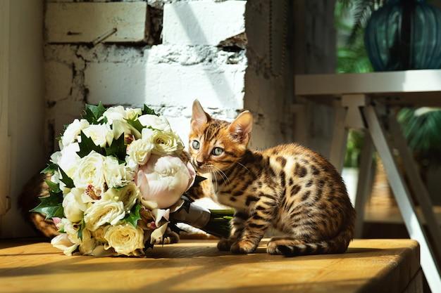 Gatito de bengala curioso que huele el ramo de flores que se sienta en la mesa cerca de la ventana en casa