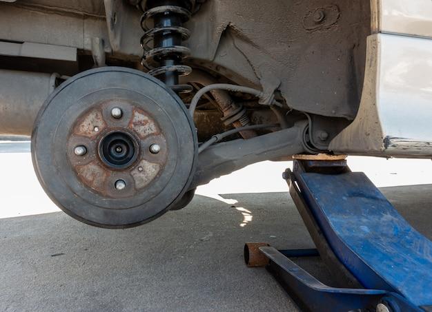 El gato hidráulico levanta el automóvil sucio sin rueda para reparar el neumático