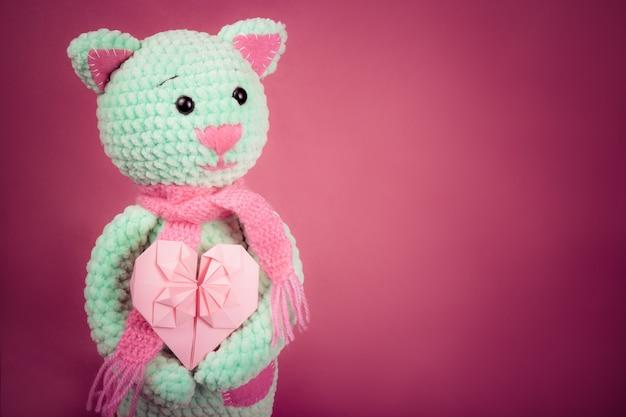 Gato de punto suave y tarjeta de san valentín sobre fondo rosa.