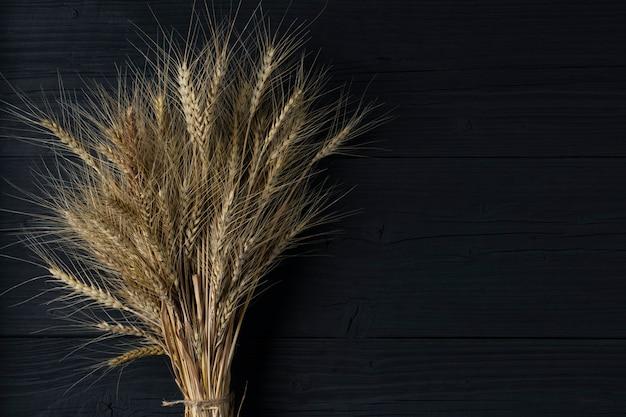 Gavilla de trigo sobre una mesa de madera negra.