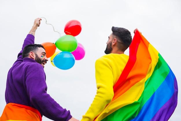 Gays con bandera arcoiris y globos disfrutando de desfile.