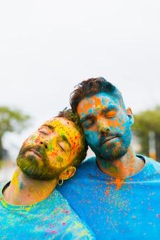 Gays cansados que se apoyan el uno al otro después de la celebración de holi