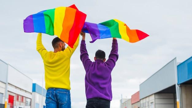 Gays sosteniendo en alto banderas ondeantes de arcoiris