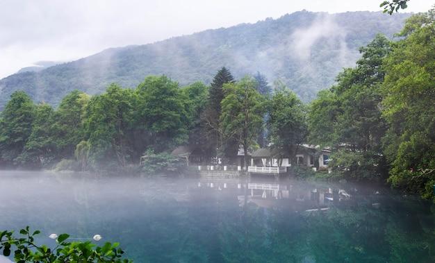 Gazebo para relajarse en la orilla del lago kárstico azul cerik-kel en tiempo nublado y brumoso, república kabardino-balkar, rusia