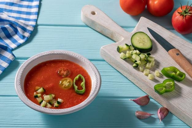 Gazpacho andaluz es una sopa fría de tomate andaluz de españa con pepino, ajo, pimiento sobre una mesa azul claro