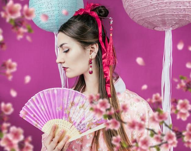 Geisha en kimono rosa y con un abanico de cerca en una pared morada y con flores de sakura borrosas