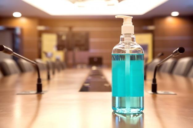 Gel de alcohol sobre la mesa en la sala de juntas.
