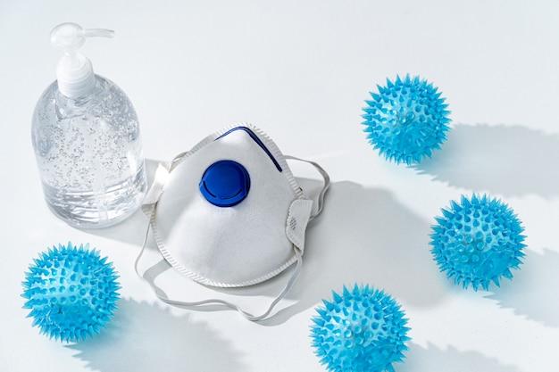 Gel antiseptico para manos y mascarilla n95 en mesa blanca con juguete de virus de punta covid-19 de goma