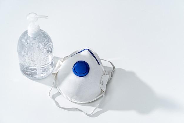Gel antiseptico para manos y mascarilla n95 en mesa blanca