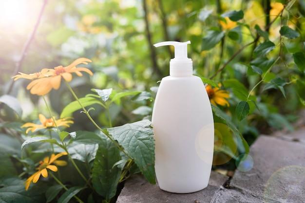 Gel de baño orgánico o champú sobre fondo de naturaleza con flores.