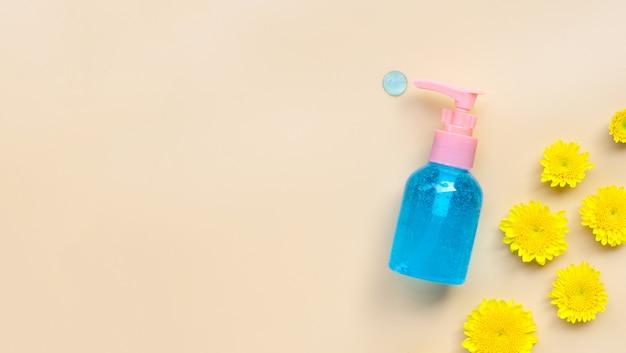 Gel desinfectante para manos en alcohol en frasco bomba con flor amarilla sobre crema