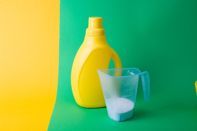 Gel de lavado y una taza medidora con detergente en polvo