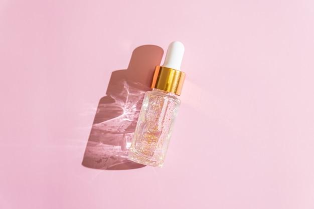 Gel líquido de oro de 24k o suero de tratamiento facial sobre fondo rosa. producto cosmético de rutina para el hogar de lujo