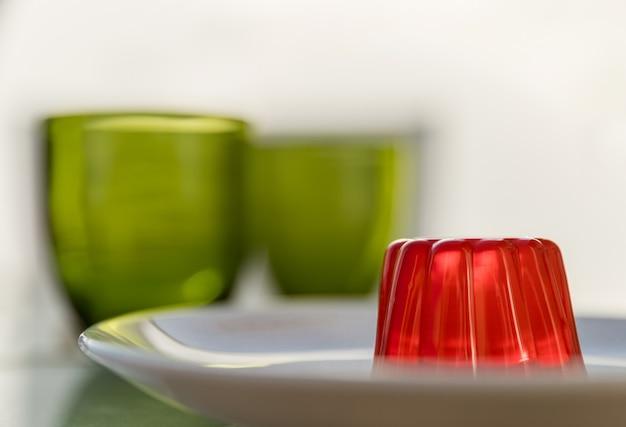 Gelatina de fresa en un plato blanco y dos vasos verdes en el fondo